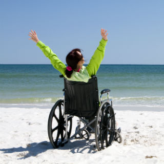 A woman in a wheelchair on the beach.