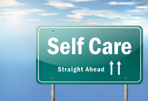 "A road sign displaying ""Self Care Straight Ahead"""